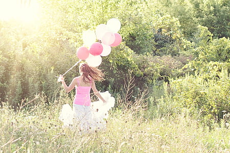 woman holding white and pink balloons
