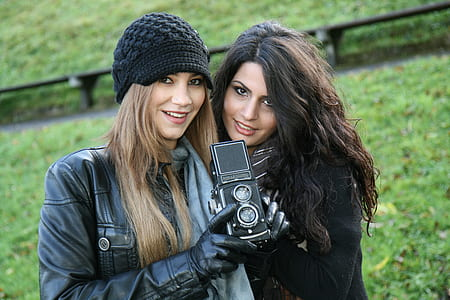 photography of two women holding camera