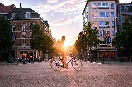 man on bicycle on the road during sunset