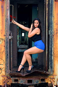 woman in blue short shorts leaning on the door