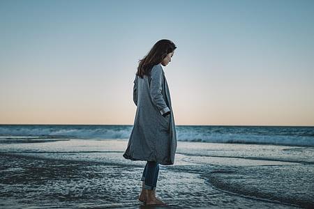 woman wearing gray coat standing on seashore
