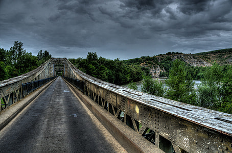 landscape photography of gray and white bridge under dark clouds