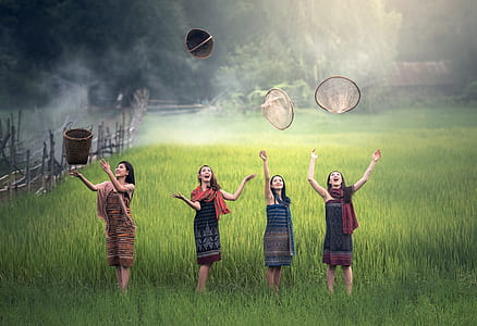 four women on rice field throwing baskets at daytime