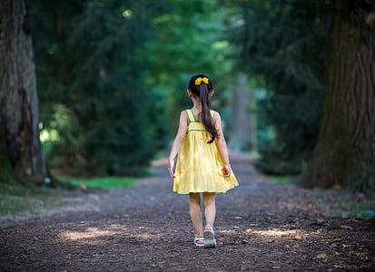 girl in yellow dress standing between trees pathway