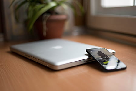 Smartphone Beside Silver Macbook on Brown Wooden Table With Potted Plant in the Background