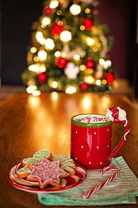 red ceramic mug beside cookies on saucer