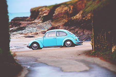 teal Volkswagen Beetle parked on seashore at daytime