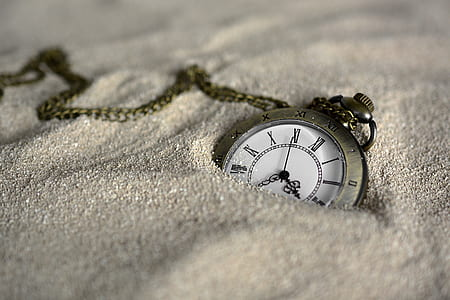 shallow focus photography of pocket watch on white sands