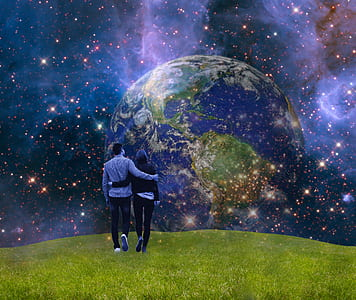 person standing on green field with universe wallpaper
