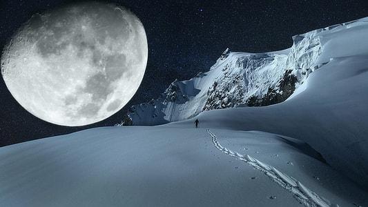 person walking on snow under moon on dark sky