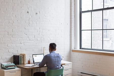 man sitting on green chair while using his laptop near the window
