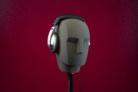 photo of black corded headphones with holder