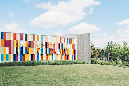 multi-colored Museum outdoor wall surrounded by green grass under blue cloudy sky
