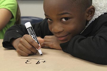 boy wearing black parka coat writing with marker