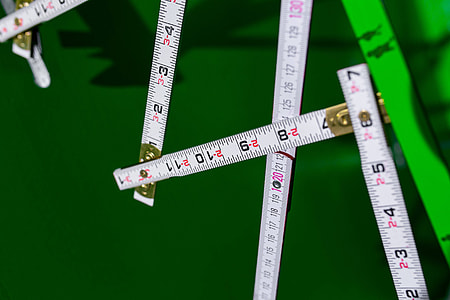 Extandable wooden ruler on a green background