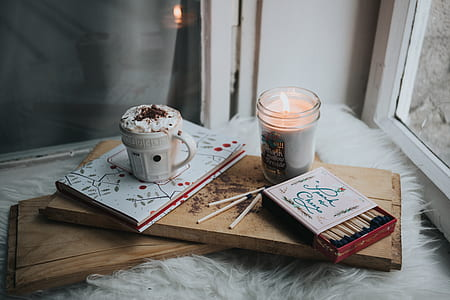 flat lane photograph of votive candle; match box; cup of beverage