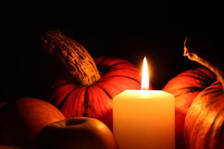 white votive candle beside pumpkins