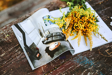 Yellow flowers with miscellaneous items on wooden floor