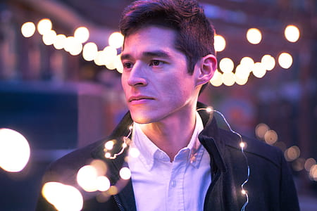 man in white collared shirt with black jacket with string lights