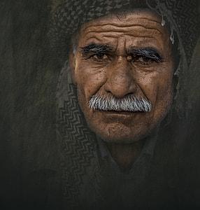 sepia photography of man wearing black cap