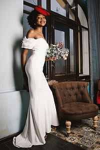 Woman in White Off-shoulder Gown Holding Bouquet of White Flowers